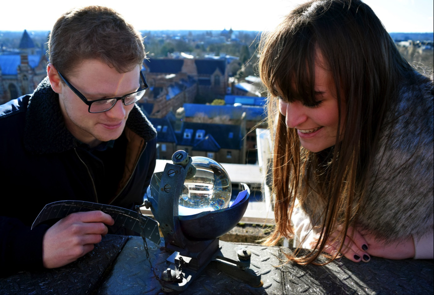 Current RMS Met Observers Callum Munday and Amy Creese record the hours of sunshine at the top of the Department of Engineering Science.
